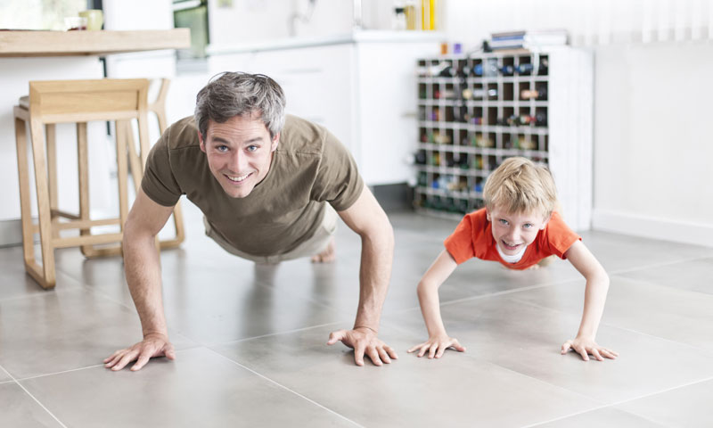 Father and son doing push-ups in kitchen