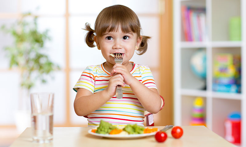 Little girl eating a healthy plate of veggies