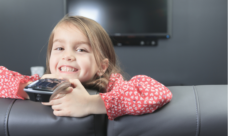 little girl with remote control in front of TV.