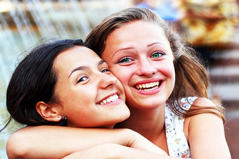 two teen girls hugging and smiling