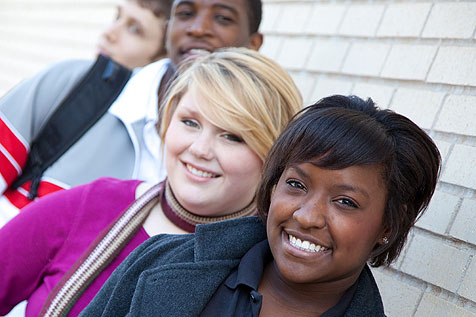 diverse group of teens standing against a wall smiling