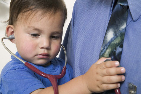Toddler using stethoscope on adult holding him