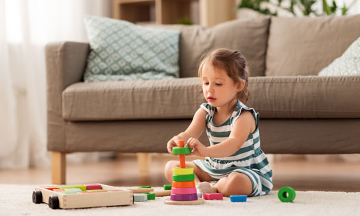 Little girl sitting on the floor playing with her toys