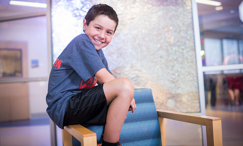 Patient Evan sitting on the arm of a chair smiling