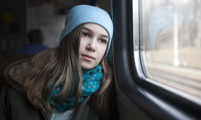 teenage girl sitting on train looking out the window