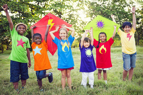 group of diverse kids holding up colorful kites