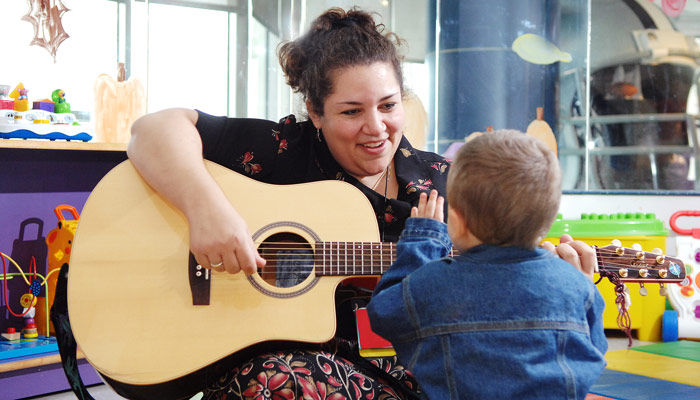 music therapist playing guitar and singing to child