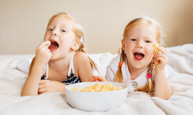 Little girls eating snack on bed
