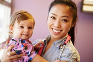 Nurse holding little toddler girl smiling