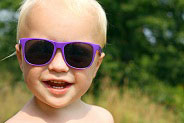 blonde toddler wearing purple sunglasses outside