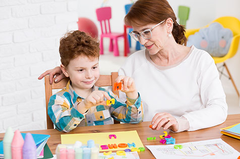 autistic boy working with tutor
