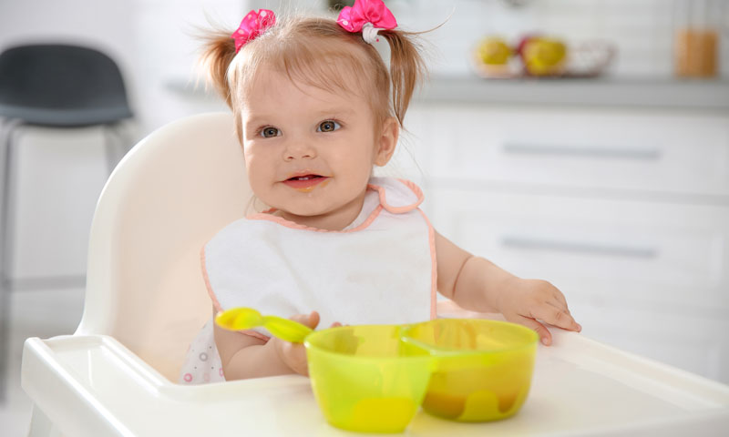 Baby eating in her high chair out of a plastic storage container