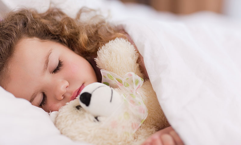 little girl sleeping holding a teddy bear