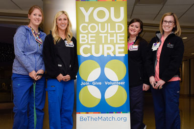 individuals standing in front of the be the match sign