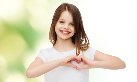 smiling little girl making heart-shape gesture with hands