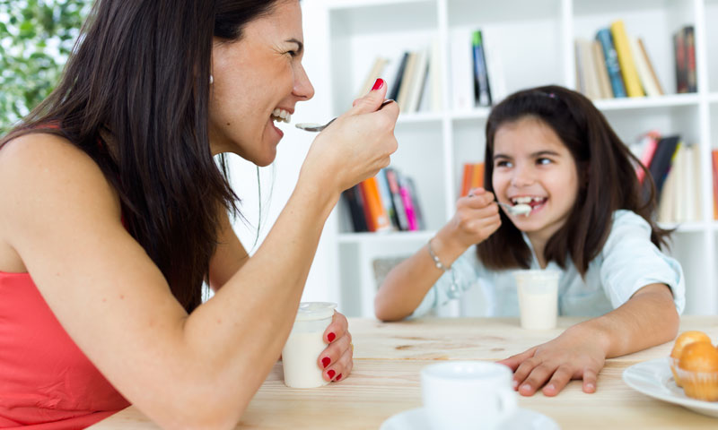Mother and her daughter eating yogurt for breakfast together