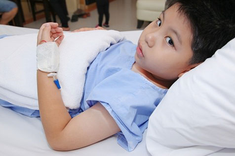 Asian boy in hospital bed