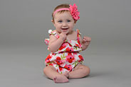 baby girl sitting on floor in floral dress and headband