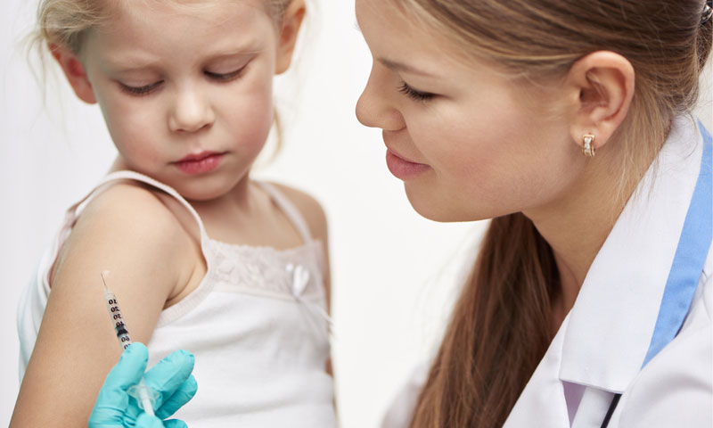 Female physician vaccinating little child