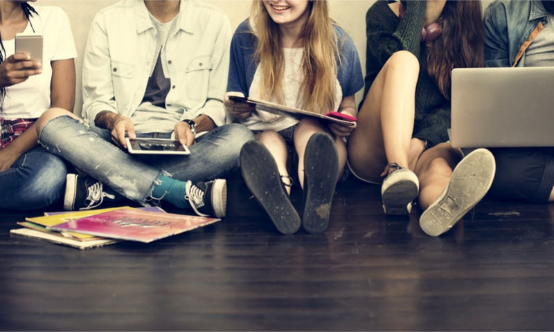 a group of teens sitting on the floor using their electronic devices
