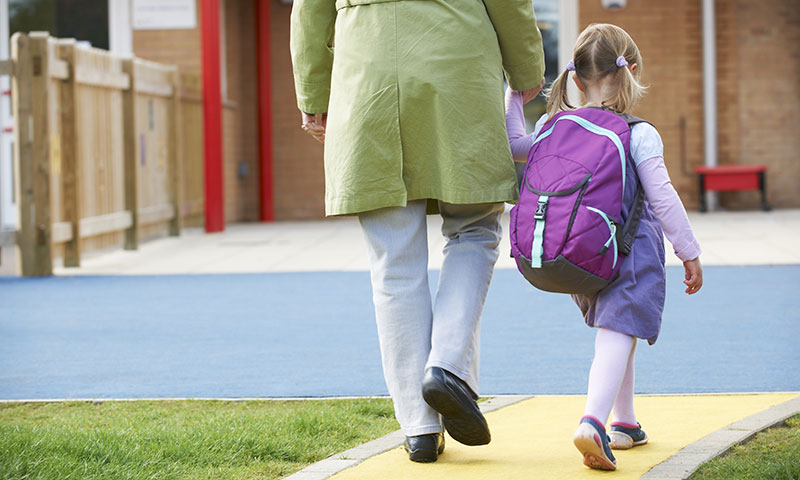 little girl walking to school with mother