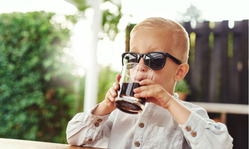 Young boy sitting on an outdoor patio sipping a soft drink