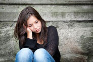 teenage girl sitting against wall looking sad