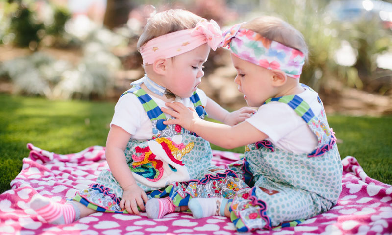 Twins Cora and Farrah sitting on a picnic blanket outside
