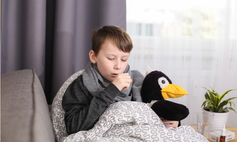 Young boy wrapped in a blanket, sitting on the couch holding a stuffed animal