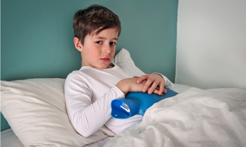 Young child is in bed sick holding a hot water bottle to his belly