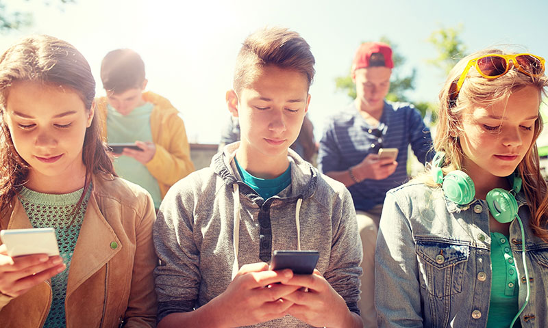 Teens staring at their phones