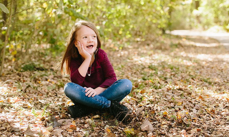 patient, Bridget sitting on some leaves in the park during fall
