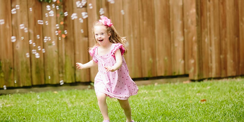 little girl running to catch bubbles