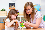 teacher building something with little girl