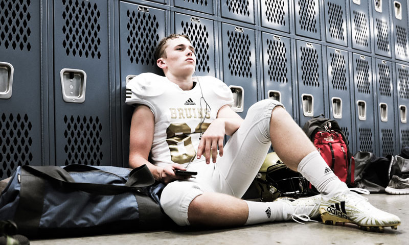 Hunter sitting against lockers in locker room
