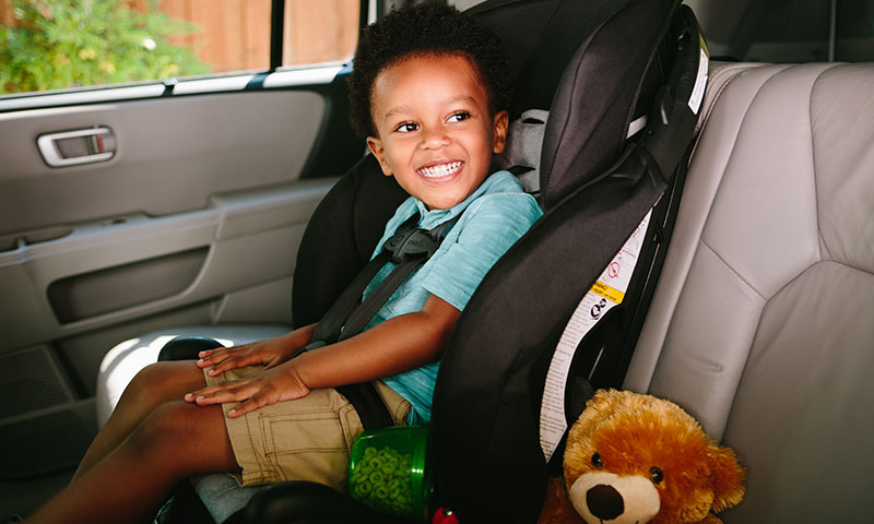 Toddler leaning standing holding onto a carseat
