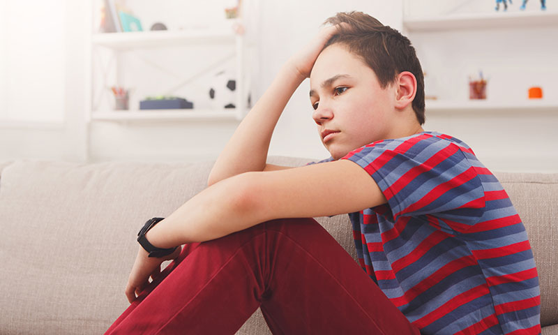 Teenage boy sitting holding his head
