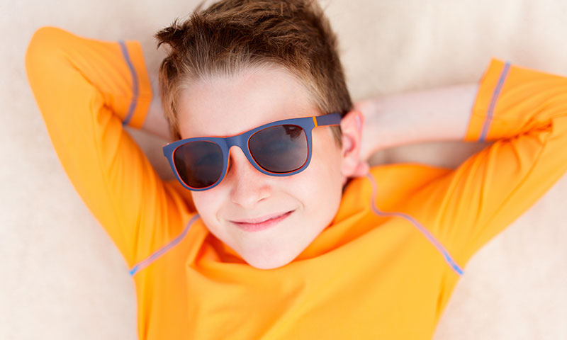 Little boy in rash guard outside wearing sunglasses