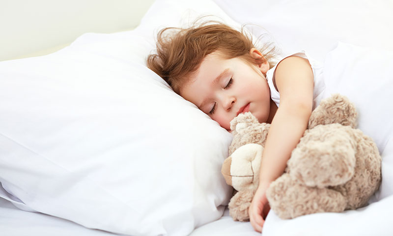 little girl sleeping with her teddy bear