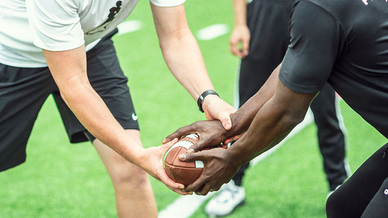 the hands of two football players handing off the ball