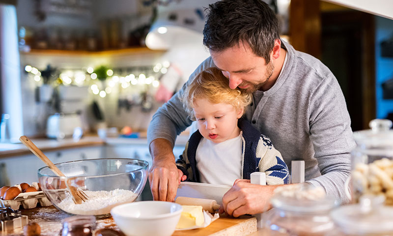 single father making holiday cookies with son