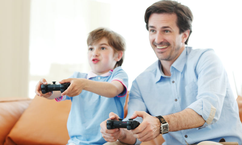 Father and son playing video games together and having fun