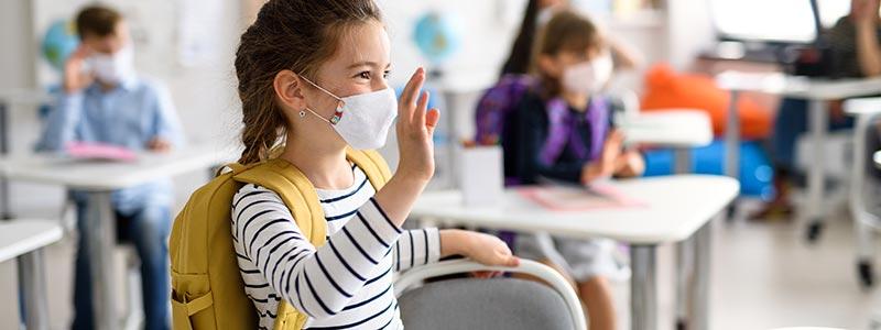 Adolescentes regresando a la escuela con su mascarilla puesta