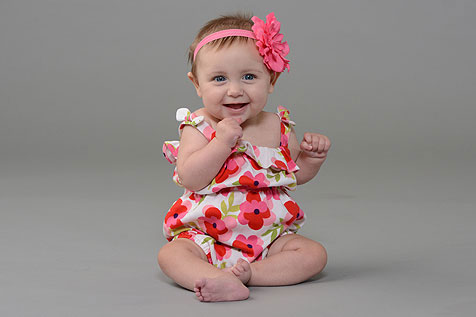 Infant girl sitting up in floral outfit