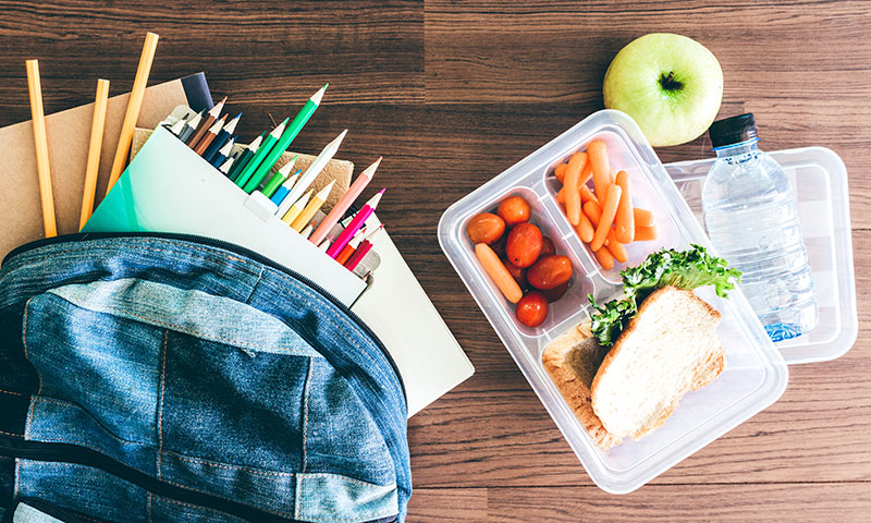 back pack with school supplies next to a nutritional lunch