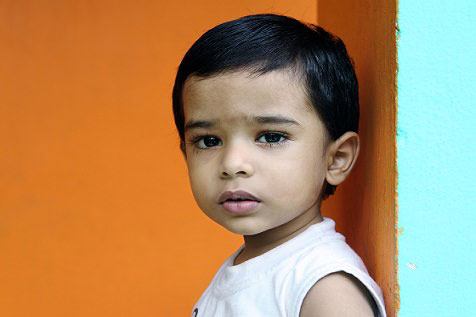 Hispanic boy standing against orange wall with serious face