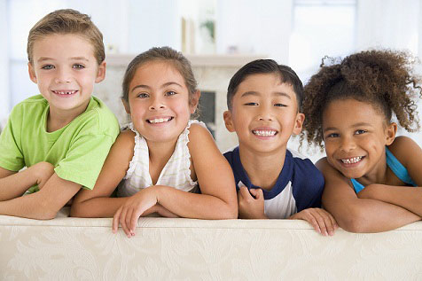 Kids leaning over edge of couch smiling