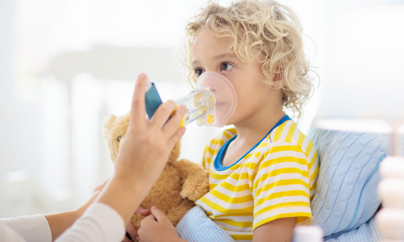 little girl using asthma inhaler at home
