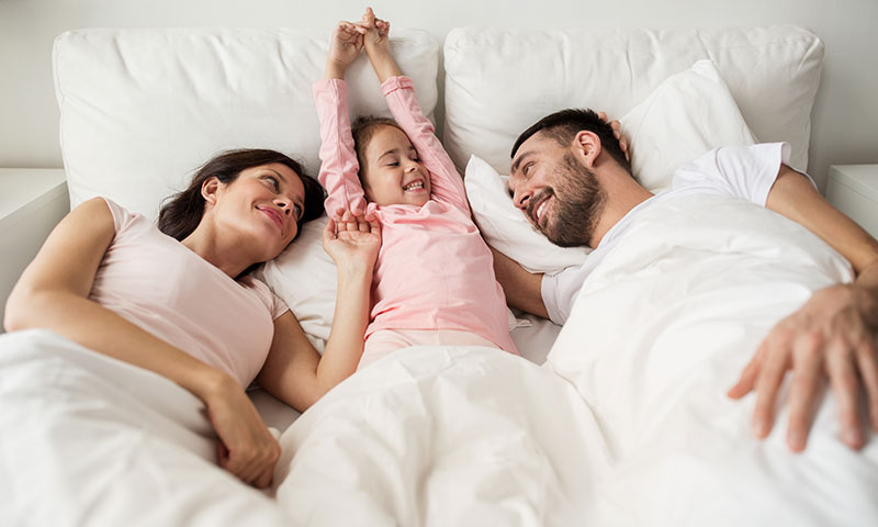 Family in bed together waking up