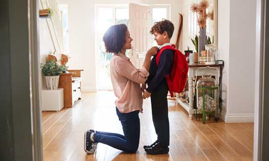 boy holding mothers hand outside of school